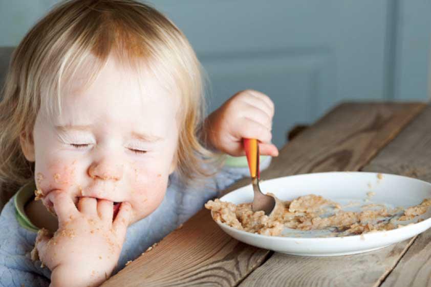 Kind beim Essen mit geschlossenen Augen